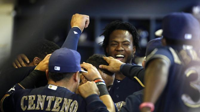 Players congratulate Milwaukee Brewers' Khris Davis in the dugout after umpires originally called him for not touching home plate after hitting a home run during the first inning of a baseball game against the San Francisco Giants Monday, May 25, 2015, in Milwaukee. The ruling was reversed after it was reviewed. (AP Photo/Morry Gash)