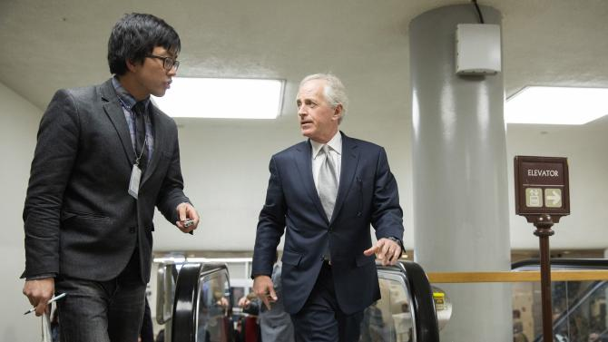 Senator Bob Corker (R-TN)(R) speaks with a reporter as he walks to the Senate Chamber to vote on legislation for funding the Department of Homeland Security