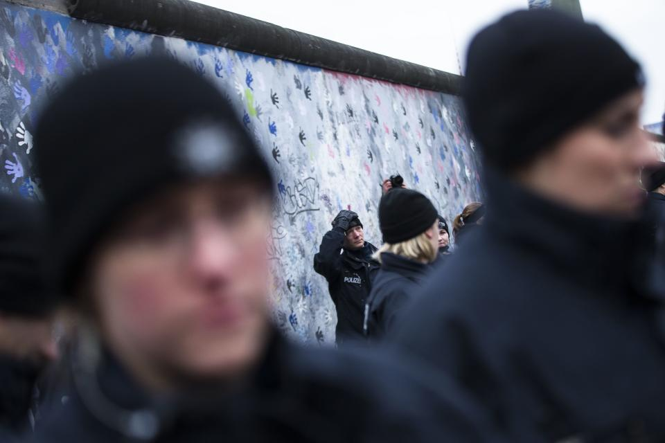 German police officers reacts as they protect a part of the former Berlin Wall in Berlin, Germany, Friday, March 1, 2013. Construction crews stopped work Friday on removing a small section from one of the few remaining stretches of the Berlin Wall to make way for a condo project after hundreds of protesters blocked their path.(AP Photo/Markus Schreiber)