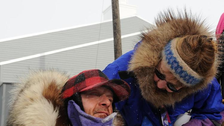 Kathy Chapoton, right, greets her husband, Martin Buser, after his sixth-place finish in the 2014 Iditarod Trail Sled Dog Race, Tuesday, March 11, 2014, in Nome, Alaska. (AP Photo/Anchorage Daily News, Bob Hallinen)