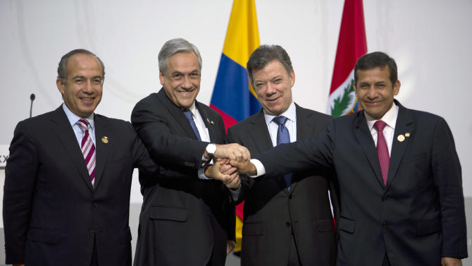 Latin-American presidents, of Mexico, Felipe Calderon; Chile, Sebastian Pinera; Colombia, Juan Manuel Santos and Ollanta Humala, of Peru, from left to right, join their hands after a meeting at the XXII Iberoamerican summit in the southern Spanish city of Cadiz, Saturday, Nov. 17, 2012. (AP Photo/Emilio Morenatti)