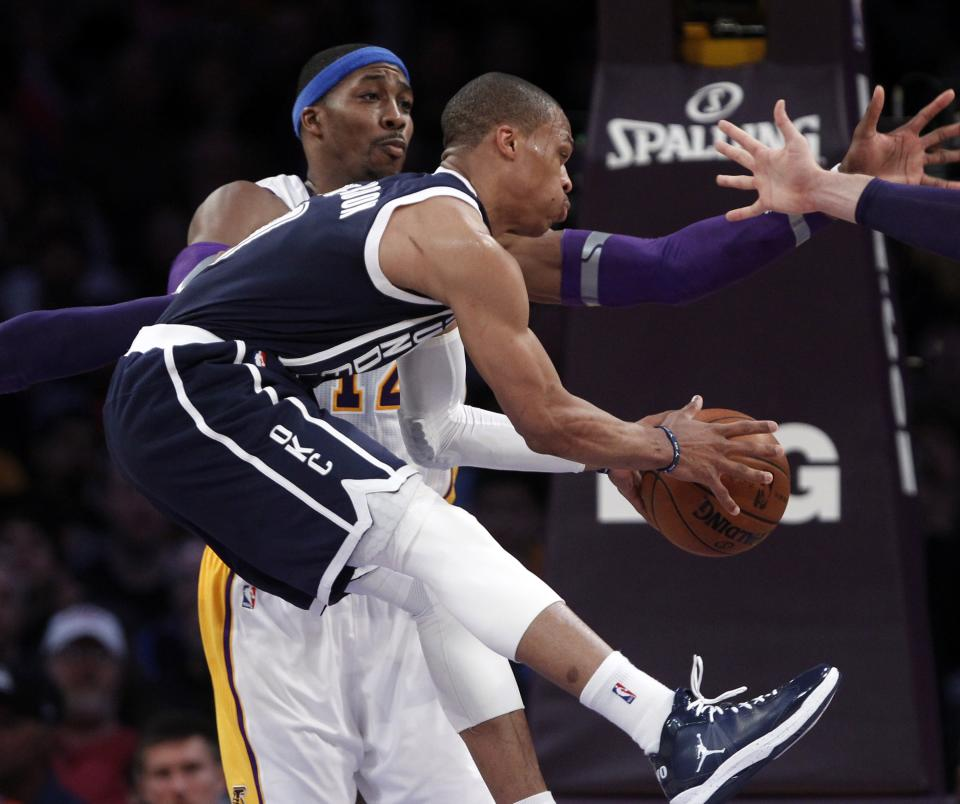 Oklahoma City Thunder guard Russell Westbrook,front, passes as Los Angeles Lakers center Dwight Howard (12) defends in the first half of an NBA basketball game in Los Angeles Sunday, Jan. 27, 2013. (AP Photo/Reed Saxon)