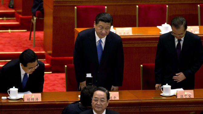 Chinese President Hu Jintao, left, Communist Party chief and incoming-President Xi Jinping, center, and Chinese Premier Wen Jiabao, right, take their seats while Yu Zhengsheng, front, chairman of the Chinese People's Political Consultative Conference prepares to begin the closing session of the annual CPPCC held inside Beijing's Great Hall of the People, in China, Tuesday, March 12, 2013. (AP Photo/Alexander F. Yuan)