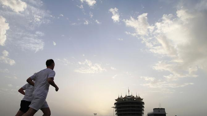 Formula One team members take a run on the Bahrain International Circuit track in Sakhir, Bahrain, on Wednesday, April 17, 2013. The F1 Bahrain Grand Prix will be held Sunday. (AP Photo/Hasan Jamali)