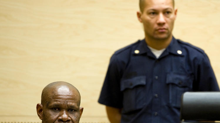 Former leader of the National Integrationist Front Mathieu Ngudjolo, left, awaits his verdict at the International Criminal Court (ICC) in The Hague, Netherlands, Tuesday, Dec. 18, 2012. The ICC acquitted Ngudjolo of all charges of leading fighters who destroyed a strategic village in eastern Congo, hacking to death and raping some 200 people including women and children in 2003. Tuesday's acquittal is only the second verdict in the court's 10-year history and the first time it has cleared a suspect. (AP Photo/Robin van Lonkhuijsen, Pool)