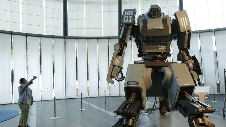 """A man takes a picture of a giant """"Kuratas"""" robot at an exhibition in Tokyo"""