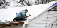 A residents makes quick temporary repairs to his roof Monday, Feb. 11, 2013, which was damaged from the Sunday&#39;s tornado in Hattiesburg, Miss. About 200 homes and mobile homes were damaged or destroyed. Rain fell today as people tried to put tarps over leaky roofs and move belongings to dry ground. (AP Photo/Rogelio V. Solis)