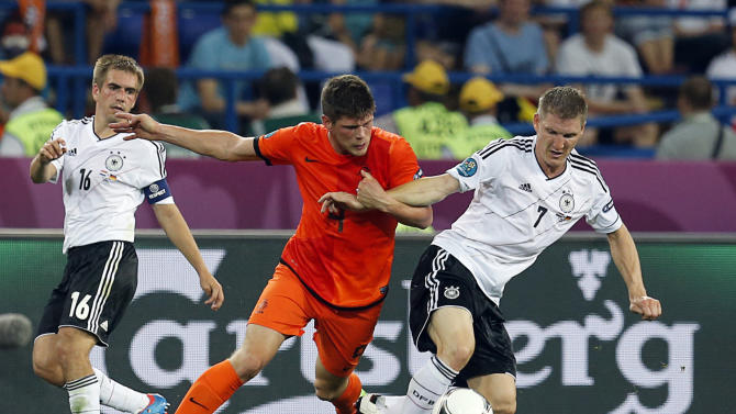 Klaas-Jan Huntelaar from the Netherlands, left, and Germany's Bastian Schweinsteiger fight for the ball during the Euro 2012 soccer championship Group B match between the Netherlands and Germany in Kharkiv, Ukraine, Wednesday, June 13, 2012. (AP Photo/Matthias Schrader)