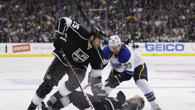 Los Angeles Kings' Trevor Lewis, bottom, falls to the ice as he and teammate Dustin Penner, left, fight for the puck with St. Louis Blues' Jordan Leopold during the second period in Game 3 of a first-round NHL hockey Stanley Cup playoff series in Los Angeles, Saturday, May 4, 2013. (AP Photo/Jae C. Hong)
