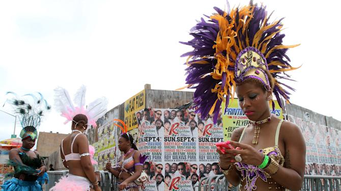 Dressed to take part in the festivities, Kylee Llewellyn, right, and others wait for the start of the West Indian Day Parade, Monday, Sept. 5, 2011, in the Brooklyn borough of New York.  (AP Photo/Tina Fineberg)