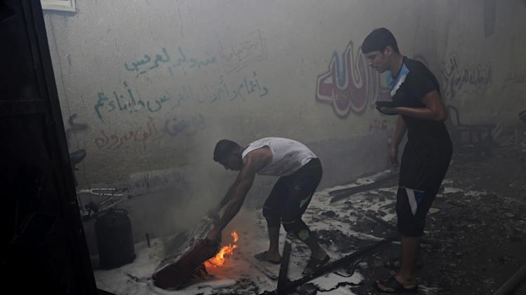 """Palestinians extinguish a fire following an Israeli strike on a building in Gaza, northern Gaza Strip, Saturday, Aug. 23, 2014. Arabic writing on wall gives congratulations from relatives on a wedding, """"a thousand congratulations."""" (AP Photo/Adel Hana)"""