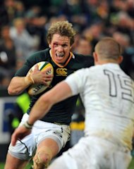 South Africa's captain Jean de Villiers (C) avoids a tackle by England's Mike Brown during their first Test match, played in Durban at Kings Park stadium, on June 9. Springboks won 22-17