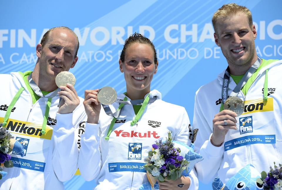 Gold medalists Germany's Thomas Lurz, left, Isabelle Franziska Harle, center, and Christian Reichert, pose with their medals after the 5km team event open water swim competition at the FINA Swimming World Championships in Barcelona, Spain, Thursday, July 25, 2013.(AP Photo/Manu Fernandez)