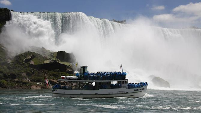 In this Friday, June 11, 2010 photo, tourists ride the Maid of the Mist tour boat at the base of the American Falls in Niagara Falls, N.Y. Gov. Andrew Cuomo has confirmed that a deal has been struck to keep the iconic Maid of the Mist scenic tour boats running from the New York side at Niagara Falls. (AP Photo/David Duprey)