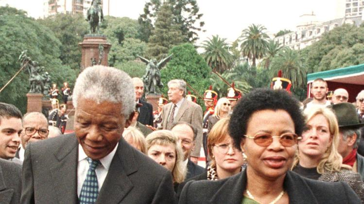 Then South African President Mandela and his wife walk away after placing flowers at a monument in Buenos Aires