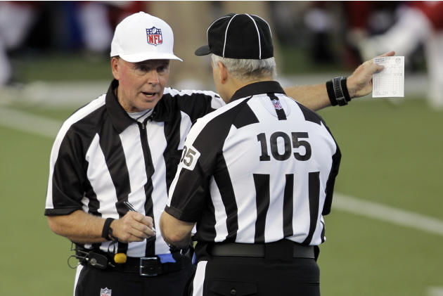 Referee Craig Ochoa, left, talks with field judge Rusty Spindel (105) during the first quarter of the NFL Hall of Fame exhibition football game between the Arizona Cardinals and New Orleans Saints, Su
