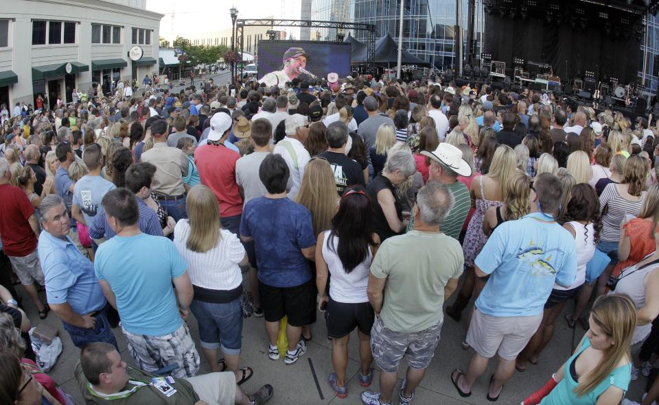 Country music fans watch Luke Bryan's performance on a giant screen as the CMT Music Awards show is shown outside Bridgestone Arena on Wednesday, June 6, 2012, in Nashville, Tenn. (AP Photo/Mark Humphrey)