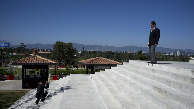 In this Nov. 20, 2012 photo, a private security guard poses for photos for a colleague on the steps of the city hall in Paseo Cayala, a nearly independent city on the edges of Guatemala City. Unlike most upscale malls and other shops in the capital, where private guards openly tote rifles, here security guards carry concealed pistols, wear suits and small earpieces with clear cords. (AP Photo/Moises Castillo)