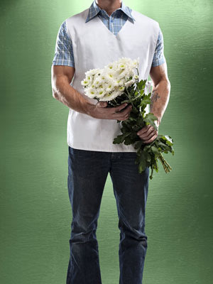 Man holding flowers towards someone.