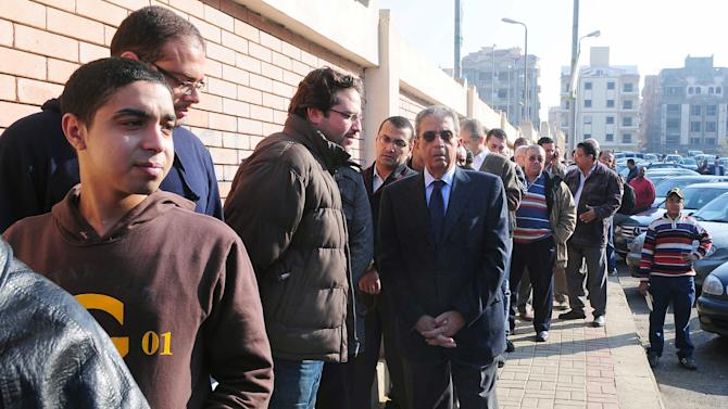 FILE - In this Nov. 28, 2011 file photograph, Egyptian presidential hopeful Amr Moussa, center, waits outside a polling station before voting on the first day of parliamentary elections in Cairo, Egypt. In the race to become the first president of the new Egypt, the secular candidate with the strongest chance of beating increasingly powerful Islamists has to overcome the baggage he brings from the old Egypt. On the campaign trail ahead of next month's landmark vote, the 76-year-old Amr Moussa presents himself as an elder statesman with years of experience in politics and government, first from a decade as foreign minister under former President Hosni Mubarak, then from another decade leading the Arab League. (AP Photo/Hossam Ali, File)