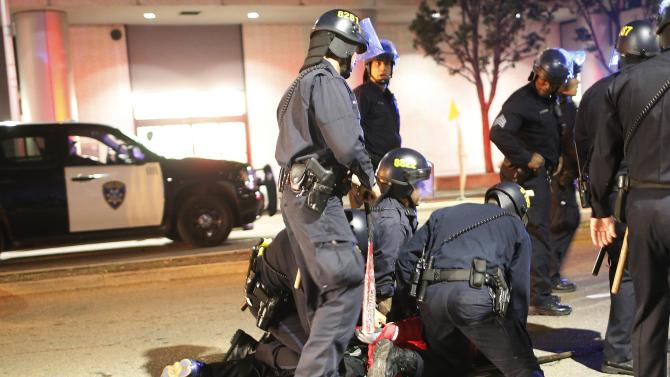 A police officer holds a baseball bat taken from a detained protester in Oakland
