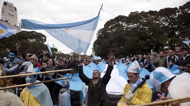 Soccer fans play instruments and wave Argentine flags as they arrive to watch Argentina's World Cup match with Iran on an outdoor screen set up in Buenos Aires, Argentina, Saturday, June 21, 2014. (AP Photo/Eduardo Di Baia)
