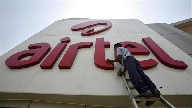A worker cleans a logo of Bharti Airtel at its zonal office building in Chandigarh May 2, 2013. REUTERS/Ajay Verma/Files