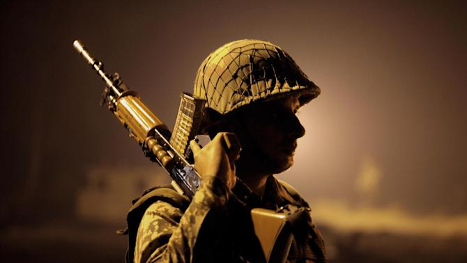 An Indian Border Security Force (BSF) soldier stands guard during a night patrol near international border fencing at Suchet Garh in Ranbir Singh Pura, about 27 kilometers (17 miles) south of Jammu, India, Thursday, Jan. 10, 2013. The Pakistani army accused Indian troops of firing across the disputed Kashmir border and killing a soldier Thursday, the third deadly incident in the disputed Himalayan region in recent days. (AP Photo/Channi Anand)