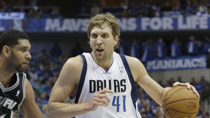 In this April 26, 2014 file photo, Dallas Mavericks forward Dirk Nowitzki (41) drives against San Antonio Spurs forward Tim Duncan during the first half of Game 3 of an NBA basketball first-round playoff series in Dallas. Nowitzki talks and acts like he's under contract with the Mavericks even when he's not. So while the signing of his fifth and possibly final deal with Dallas is a foregone conclusion early next month, the shape of things around the 36-year-old is the biggest question starting with the NBA draft Thursday night, June 26