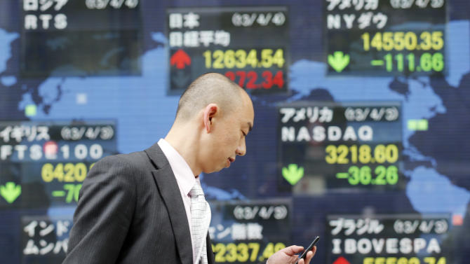 "A man checks his mobile phone as he walks by an electronic stock board of a securities firm in Tokyo showing Japan's benchmark Nikkei 225 stock index, center top, that gained 272.34 points to 12,634.54 Thursday, April 4, 2013. Earlier in the day the Bank of Japan announced a policy overhaul intended to double the money supply and achieve a 2 percent inflation target at the ""earliest possible time, with a time horizon of about two years."" Financial markets reacted with relief. (AP Photo/Koji Sasahara)"