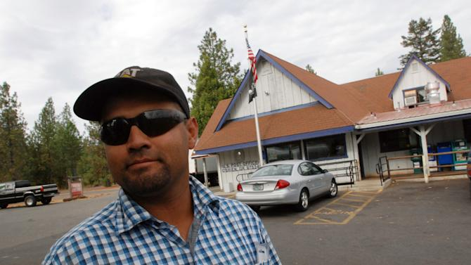In this Oct. 12, 2012, photo, Hector Guzman poses for a photo in front of the post office in O'Brien, Ore., where cuts to sheriff's patrols prompted by the failure of a tax levy have inspired some local residents to organize armed patrols of the rural area of about 750 residents. Guzman, whose home was burglarized several years ago, said he likes the idea of people watching out for each other. (AP Photo/Jeff Barnard)