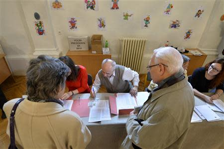Members of an election committee prepare ballots for voters at a polling station during the first round presidential elections in Bratislava