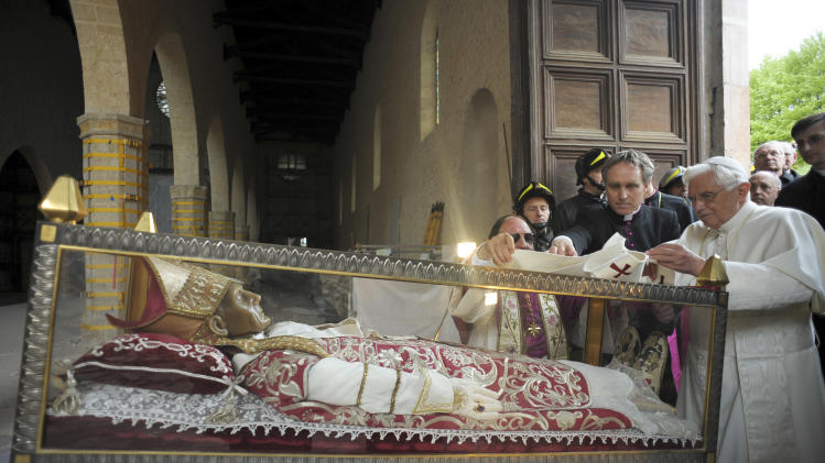 FILE - In this April 28, 2009 file photo provided then by the Vatican newspaper L'Osservatore Romano, Pope Benedict XVI stands by the salvaged remains of Pope Celestine V, in the 13th-century Santa Maria di Collemaggio Basilica, the symbol of the city of L'Aquila, whose roof partially caved in during the quake. Benedict XVI announced Monday, Feb. 11, 2013 that he would resign on Feb. 28 because he was simply too infirm to carry on - the first pontiff to do so in nearly 600 years. The decision sets the stage for a conclave to elect a new pope before the end of March. Pope Celestine V, the 13th-century hermit and saint, was one of the earlier popes to resign. (AP Photo/L'Osservatore Romano, file)