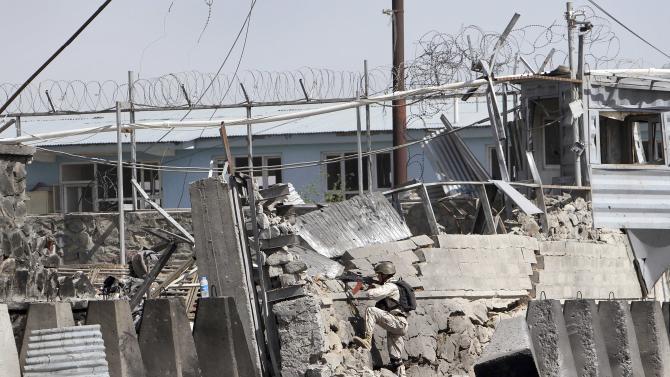 An Afghan police special force member mans a compound at the scene of militants attack, in Kabul, Afghanistan, Wednesday, May 2, 2012. A suicide car bomber and Taliban militants disguised in burqas attacked the compound housing hundreds of foreigners on Wednesday, officials and witnesses said. The Taliban said the attack was a response to President Barack Obama's surprise visit just hours earlier. (AP Photo/Musadeq Sadeq)