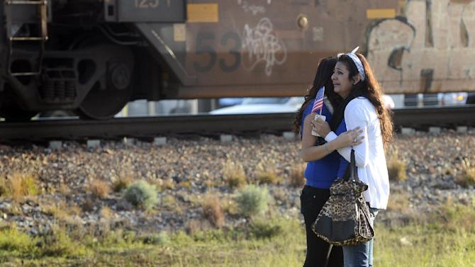 """Parade participants react after a trailer carrying wounded veterans in a parade was struck by a train in Midland, Texas, Thursday, Nov. 15, 2012. """"Show of Support"""" president and founder Terry Johnson says there are """"multiple injuries"""" after a Union Pacific train slammed into the trailer, killing at least four people and injuring 17 others. (AP Photo/Reporter-Telegram, James Durbin)"""