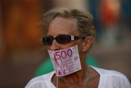 A woman covers her mouth with a fake Euro note during a protest against Spain's bailout in Malaga