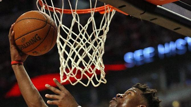 Chicago Bulls' Jimmy Butler goes up for a shot over Milwaukee Bucks' Khris Middleton on his way to a game-high 31 points during the first round of the NBA Playoffs at United Center on April 20, 2015