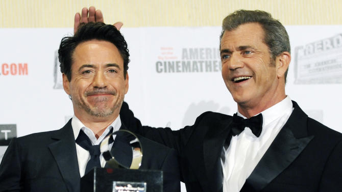 Presenter Mel Gibson, right, jokes with honoree Robert Downey Jr. during a mock presentation backstage at the 25th American Cinematheque Award benefit gala honoring Downey, Friday, Oct. 14, 2011, in Beverly Hills, Calif. (AP Photo/Chris Pizzello)
