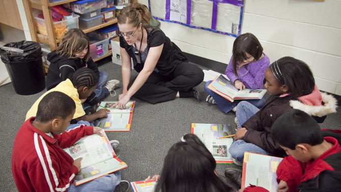 In this Jan. 23, 2013 photo, Jefferson Elementary third grade teacher Delilah Crossette reads with her students at Jefferson Elementary in Wichita, Kan.  Kansas is one of an increasing number of states that are not promoting students who are struggling to read at the end of third grade. Thirty-two states have passed legislation designed to improve third-grade literacy, according to the Education Commission of the States.(AP Photo/Mike Hutmacher) LCOAL TV OUT; MAGS OUT; LOCAL RADIO OUT; LOCAL INTERNET OUT