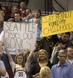 FILE - In this Feb. 11, 2009, file photo, Seattle SuperSonics fans show their displeasure when the Oklahoma City Thunder, formerly the SuperSonics, were introduced during an NBA basketball game against the Portland Trail Blazers,  in Portland, Ore.  Before they became critically acclaimed documentary filmmakers, Adam Brown and Jason Reid, not shown, were simply basketball junkies. And being hoops aficionados, Brown and Reid can appreciate the way the Oklahoma City Thunder play on the court.  But all it takes is one screen shot of owner Clay Bennett or one mention of the Thunder's past incarnation as the Seattle SuperSonics to help them recall why they can never cheer for that team.(AP Photo/Don Ryan, file)