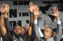 """Father of slain teen Michael Brown, Michael Brown, Sr., left, and Reverend Al Sharpton, right, gesture to the crowd at Peace Fest, Sunday, Aug. 24, 2014, in St. Louis. Tomorrow all I want is peace,"""" Brown Sr. told hundreds of people in St. Louis' largest city park Sunday during brief remarks at a festival that promoted peace over violence. (AP Photo/Bill Boyce)"""
