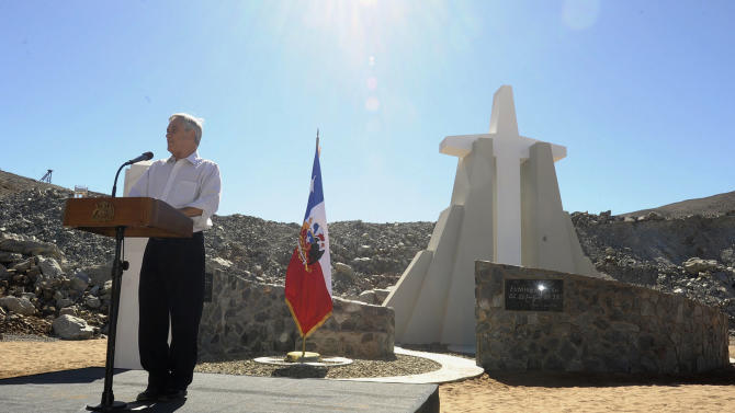 "In this photo released by Chile's Presidency, Chile's President Sebastian Pinera delivers a speech during an event marking the second anniversary of the cave-in at the San Jose mine in the Atacama, honoring the miners who survived in entrapment longer than anyone else before, in front of a monument on the outskirts of Copiapo, Chile, Sunday, Aug. 5, 2012. Pinera traveled to the northern city of Copiapo to join the men at the mouth of the mine that nearly became their rocky grave. They unveiled a five-meter (16 1/2-foot) cross as part of a monument known as the ""The 33 miners of Atacama: The miracle of life."" (AP Photo/Chile's Presidency)"