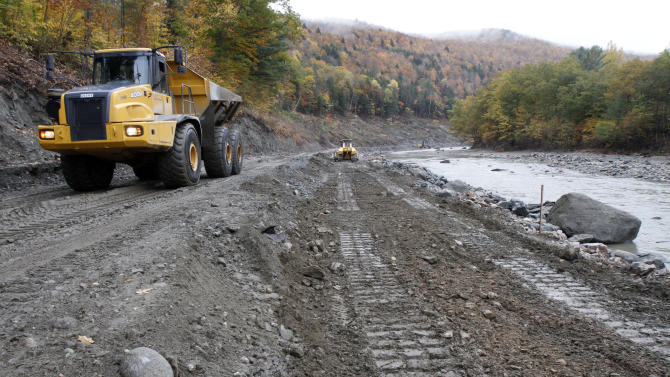 FILE - In this Oct. 14, 2011, file photo,  a rock hauler moves rocks on damaged Vermont Route 107 in Bethel, Vt. Tropical Storm Irene had a major effect on Vermont roads. Hurricane Irene and its remnants raked the Caribbean, the eastern U.S. and Canada for more than a week a year ago. Though it never hit the U.S. as anything stronger than a minimal hurricane, it ranks among the costliest in history, causing more than $5.3 billion in damage, and killed at least 67 people in all. (AP Photo/Toby Talbot)