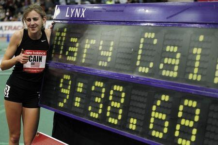 Cain poses next to her record for high school girls two mile during New Balance Indoor Grand Prix track meet in Boston