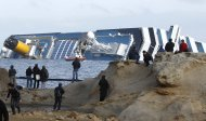 People stop and look at the grounded cruise ship Costa Concordia off the Tuscan island of Giglio, Italy, Sunday, Jan. 22, 2012. Rescuers on Sunday resumed searching the above-water section of the capsized Costa Concordia cruise liner, but choppy seas kept divers from exploring the submerged part, where officials have said there could be bodies. Civil protection officials said that until the waves slack off, divers would not swim into the submerged part of the vessel just off the port of Giglio, a tiny Island off the Tuscan coast. (AP Photo/Pier Paolo Cito)