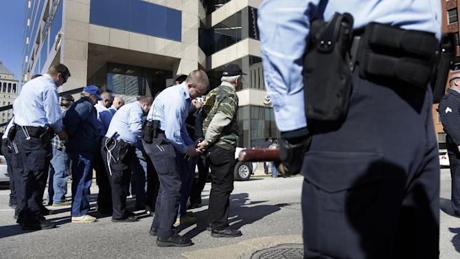 Police arrest members of the United Mine Workers of America as they take part in a protest outside the of headquarters of Peabody Energy, one of the companies the union accuses of orchestrating business deals that bankrupted Patriot Coal, Wednesday, Feb. 13, 2013, in St. Louis. Ten people were arrested during the protest of bankruptcy proceedings that the union says jeopardizes pension and health care benefits for some 20,000 retirees and dependents. (AP Photo/Jeff Roberson)