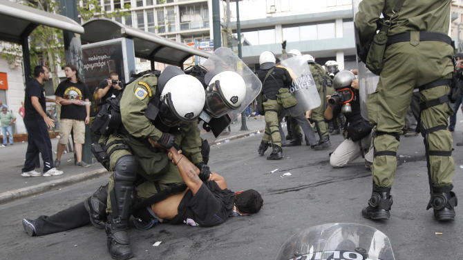 Riot police arrest a demonstrator during clashes in front of the parliament in Athens, Tuesday, Oct. 9, 2012. German Chancellor Angela Merkel got a hostile reception from ordinary Greeks Tuesday when she flew into Athens on her first visit to the country since its debt crisis erupted three years ago. (AP Photo/Nikolas Giakoumidis)
