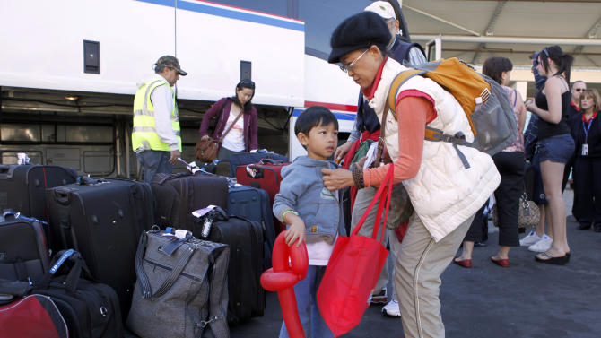 Arthur Chung, 3-1/2, or San Diego, holds a balloon animal as he is helped by his grandmother Laybal Chow as passengers from the Carnival Splendor return by bus to Long Beach, Calif., from San Diego where the cruise ship was towed after becoming disabled, Thursday, Nov. 11, 2010.  (AP Photo/Reed Saxon)