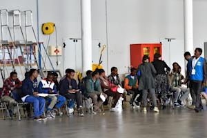 A group of Eritrean refugees prepare to board a plane …