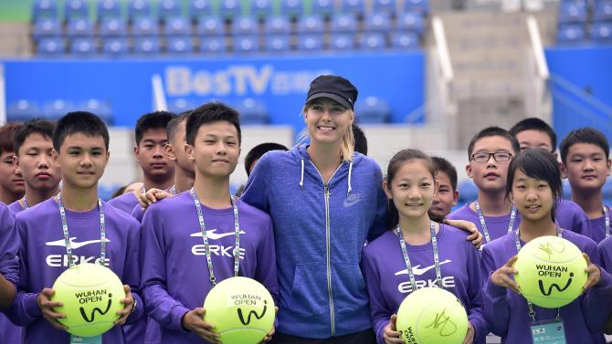 Sharapova of Russia poses for photographs with ball boys and girls during a promotional event ahead of the Wuhan Open Tennis Tournament in Wuhan